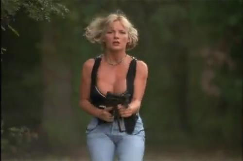 Sexy busty blonde girl shoots machine gun and shakes her boobs.