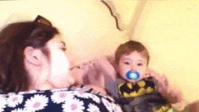 A small child crawls out and hits his mother in the face, a funny animated GIF.