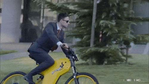 The guy is riding a yellow E-bike Greyp G12 in a business suit.